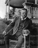 President Theodore Roosevelt sits, leaning to the left in a chair. His left elbow rests on the left arm of the chair. He is wearing a suit with riding boots and squinting into the camera.
