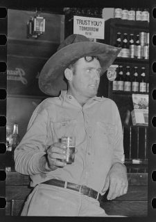 Man wearing large Stetson-style hat, leaning against a bar while holding a beer in his right hand.