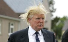 Photo of Donald Trump, wearing a suit and tie, with his hair blown around by the wind.