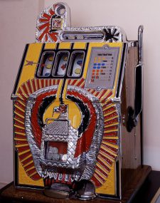 Red and yellow vintage slot machine decorated with an eagle design on the front