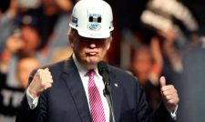 """Donald Trump wearing a white hard hat. His lips are pursed and his eyes are obscured by the shadow of the hat. He is making a """"thumbs up"""" gesture with his right hand and a fist with his left hand. There is a crown behind him but the background is blurred."""